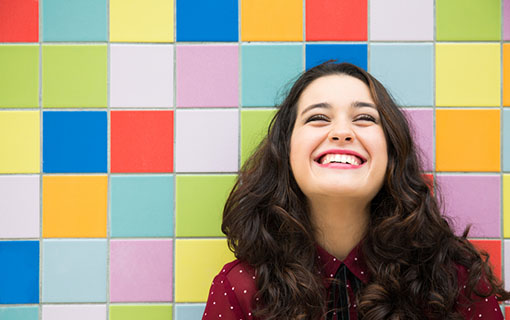 https://members.personallifemedia.com/wp-content/uploads/2018/11/Happy-girl-laughing-against-a-colorful-tiles.jpg